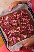 Woman holding a baking pan with rose petal cake (Hungary)