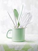 Assorted kitchen utensils in enamel cup
