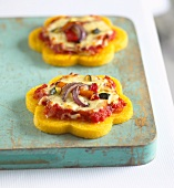 Mini polenta pizzas topped with tomatoes, cheese and onions