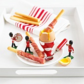 Grissini with ham, a soft boiled egg and toy figures