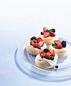 Meringue nests with berries on a glass plate