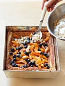 Slivered almonds being sprinkled over a fruit tart