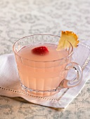 Glass of Pink Lemonade Punch with Raspberry and Pineapple Garnish