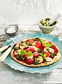 A sweet pizza topped with strawberries, marzipan and pistachio pesto