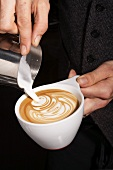 Person Pouring Cream into a Cappuccino