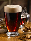Glass of Dark Beer on a Table with Nuts and Olives