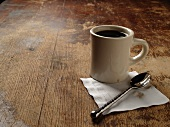 Cup of Coffee with Napkin and Spoon on a Rustic Wooden Table