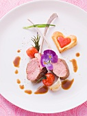 Medium rare lamb chops with heart-shaped puff pastries