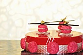Raspberry cake topped with macaroons and gold leaf