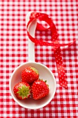 Three strawberries in a ladle