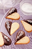 Heart-shaped biscuits decorated with chocolate icing and candied lavender flowers