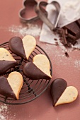Heart-shaped biscuits with chocolate icing on a wire rack