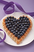 A heart-shaped blueberry tart on a plate with a purple ribbon