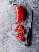 A red chilli pepper, sliced, with a knife