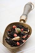 Green tea (sencha) and dried rosebuds on an old tea scoop