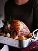 A woman holding a turkey and potatoes in a roasting tin