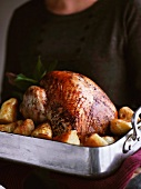 A woman a turkey and roast potatoes in a roasting tin