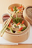 Dumplings with prawns and vegetables in a bamboo steamer