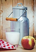 A milk churn, a glass of milk and an apple