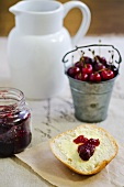 Half a bread roll topped with butter and cherry jam with a bucket of fresh cherries in the background