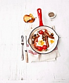 English breakfast in a pan (fried egg with sausage and tomatoes)