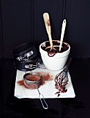 Chocolate cake mixture, a whisk, cocoa powder and a cake tin