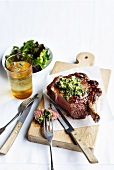 Grilled rib eye steak with sardine and caper butter
