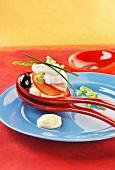 Löffelhappen mit Kabeljau, Tomatenscheibe, Kartoffelpüree, und Olive