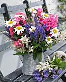 Sommerlicher Blumenstrauss im Zinkkrug auf Gartenbank