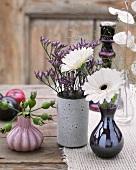 Blumenvasen und Pflaumen auf Holztisch