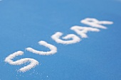 The word SUGAR written on a blue surface