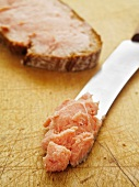 Teewurst on a knife and a slice of bread