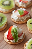 Crackers Topped with Cream Cheese, a Strawberry Slice and a Mint Leaf; Some Topped with Cream Cheese and Kiwi
