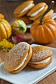 Two Pumpkin Whoopie Pies with Powdered Sugar; Gourds