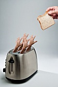 Four Hands Reaching From a Toasted to Grab a slice of Bread
