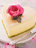 A heart-shaped cake with a white chocolate glaze and a sugared rose