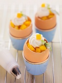 Carrot cakes baked in egg shells and garnished with mango and quark cream