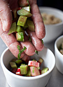 A hand holding marinated rhubarb pieces