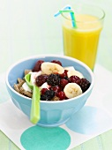 Cereals with berries and bananas and a glass of orange juice