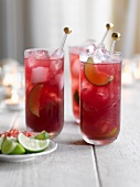 Pomegranate martinis with limes and ice cubes