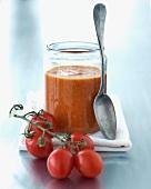 Tomatensuppe in einem Einmachglas und frische Eiertomaten