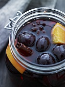 A jar of cherry compote with oranges