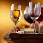 Glass of White Wine on a Table with Wine Cork, Wine Glasses and Glass of Red Wine