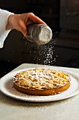 Apple tart being dusted with icing sugar