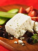 Feta, olives, cucumber and tomatoes on a chopping board