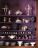 A cupboard filled with silverware and porcelain