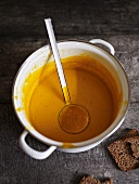 Pumpkin soup in a pot with a ladle