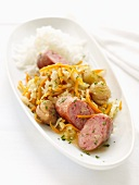 Sausage with white cabbage, carrots and a side of rice