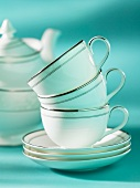 A stack of tea cups on a stack of saucers with a teapot in the background