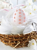 Decorated Easter egg in nest of feathers & twigs